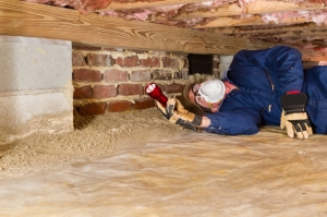 Termite inspector in residential crawl space inspects a sill for termites.